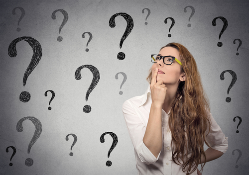 woman in glasses looking up at question marks on grey background